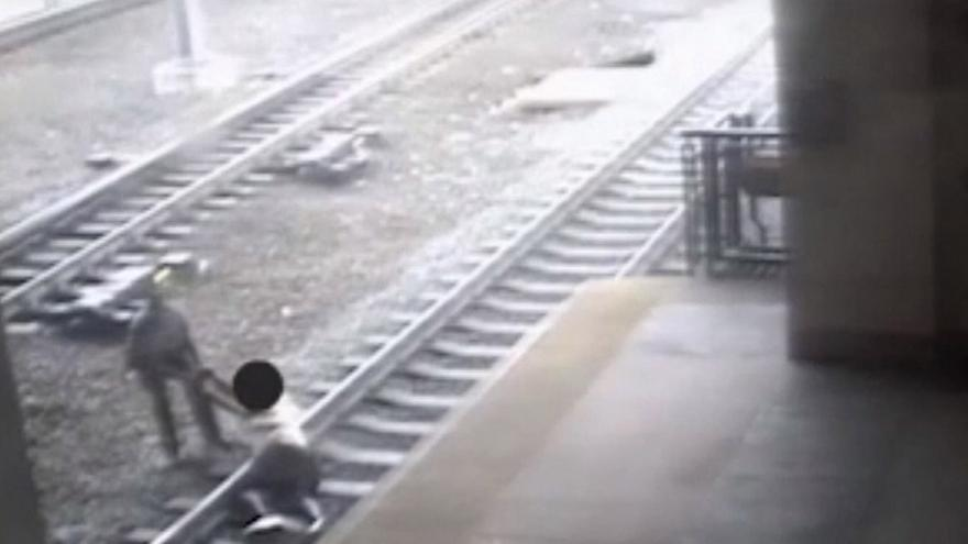 Police officer saves man from train tracks in dramatic near-miss