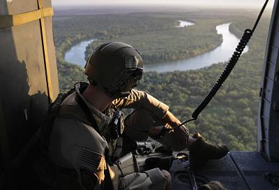 A U.S. Customs and Border Protection agent searches for undocumented immigrants during a helicopter patrol over the Rio Grande at the U.S.-Mexico border on Nov. 6, 2018 in McAllen, Texas.