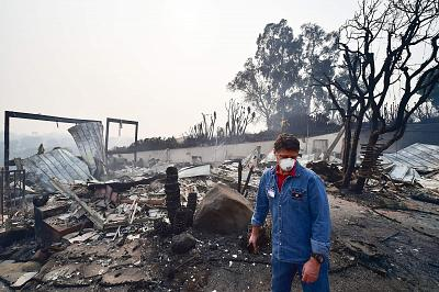 Los Angeles Sheriff\'s Department chaplain Pastor Brian La Spade walks through properties in the Points Dume neighborhood of Malibu, California, where members of his congregation live, on Nov. 10, 2018, after the Woolsey Fire tore through the neighborhood overnight.