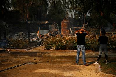 Alexander Tabolsky and Dina Arias look at the destroyed home they lived in as the Woolsey Fire continues to burn in Malibu, California on Nov. 10, 2018.