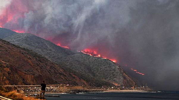 Image: A man watches as the Woolsey Fire reaches the ocean along Pacific Co