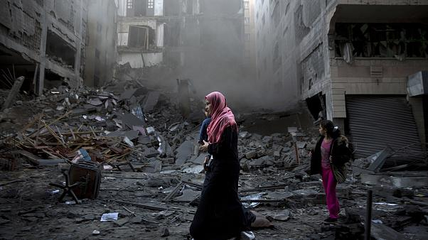 Image: A Palestinian family walks next to a destroyed residential building