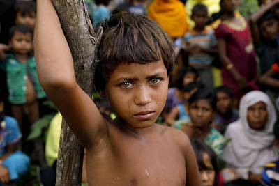 A Rohingya child stands with newly arrived refugees who fled to Bangladesh from Myanmar.