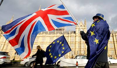 An anti-Brexit demonstrator waves a Union flag alongside a European Union flag outside the Houses of Parliament in London, on March 28, 2018.