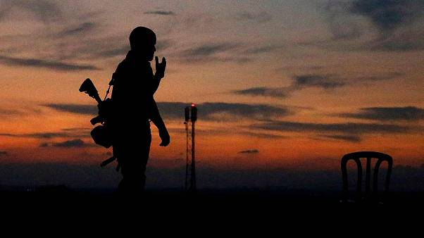 Image: The silhouette of an Israeli soldier is pictured in the southern Isr