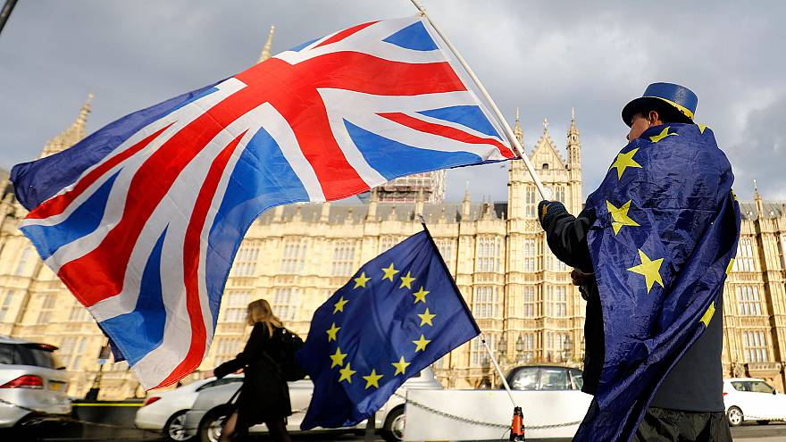 Image: An anti-Brexit demonstrator waves a Union flag alongside a European
