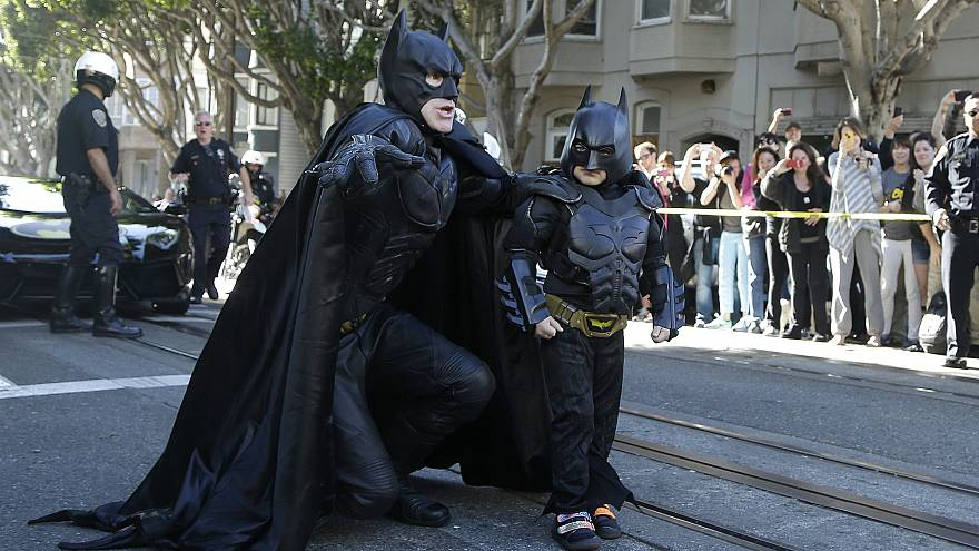 Miles Scott, dressed as Batkid, walks with Batman before saving a damsel in