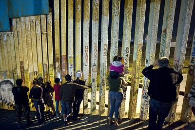 People watch a fireworks display in July through the U.S.-Mexico border wall in Tijuana, Mexico.