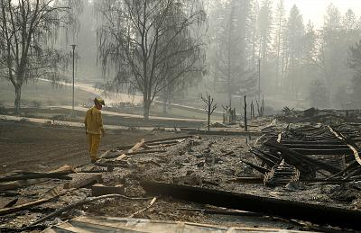 A firefighter searches for human remains in a trailer park destroyed in the Camp Fire on Nov. 16, 2018, in Paradise, California.
