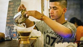 Jorge Suarez, making a coffee at his small business, the Ik-ro Cafe Bar in
