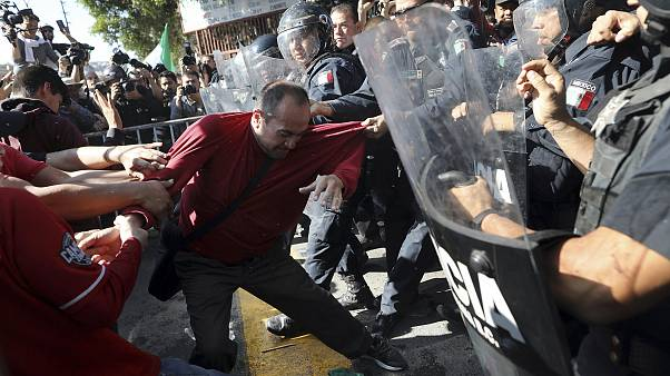 Demonstrators clash with police outside a migrant shelter as they protest t