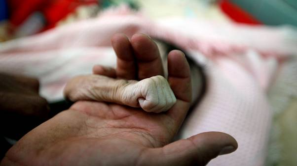Image: Saleh Hassan al-Faqeh holds the hand of his four-month-old daughter,