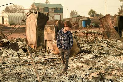 Jeremie Saylors, 11, walks through the burned remains of his home in Paradise, California, on Nov. 18, 2018. The family lost a home in the same spot to a fire 10 years prior.