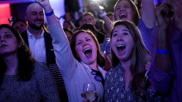 People cheer while watching live results at a midterm election night party