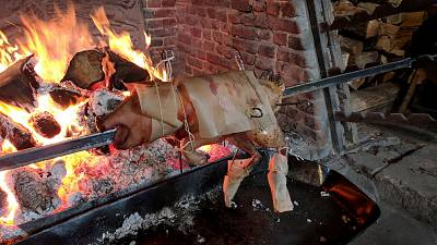 The top half of a pig is joined to legs of a turkey to create a cokyntryce, with all of it covered in buttered paper to prevent burning during roasting.