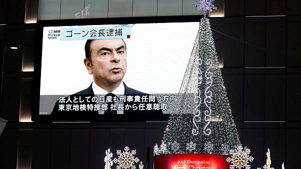 Image: A street monitor showing a news report about arrest of Nissan Chairm