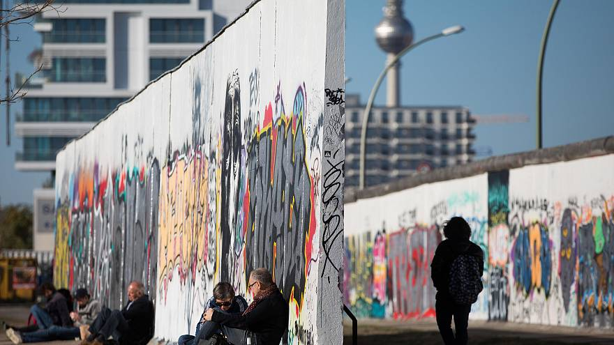 Image: People sit along the Berlin wall at the East Side Gallery in Berlin,