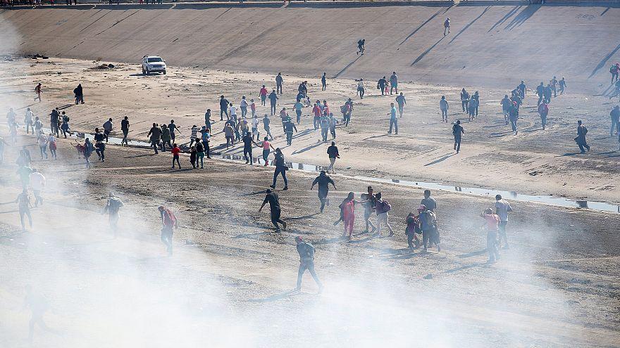 Image: Migrants run from tear gas, thrown by the U.S border patrol, near th