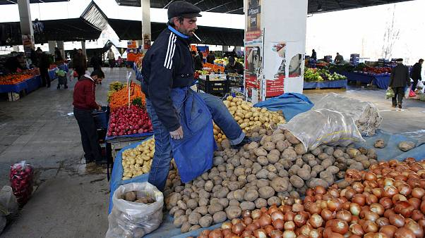 Image: A vendor sells potatoes and onions in an open market in central Anka