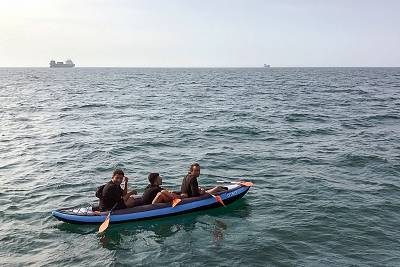 Three migrants attempting to cross the English Channel to reach Britain drift in an inflatable canoe off Calais, France, in August. They were later rescued by French authorities.
