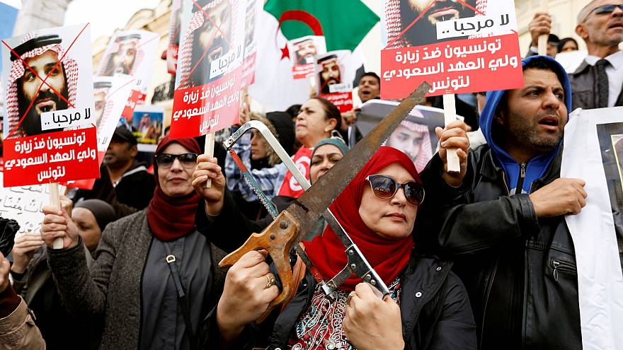 Image: Woman takes part in a protest, opposing the visit of Saudi Arabia's