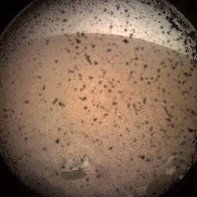 Debris speckles the protective cover over the In Sight lander\'s camera lens in the first image captured after the spacecraft touched down on Nov. 26