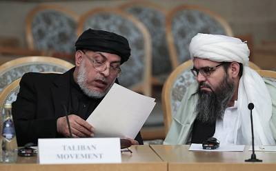 Sher Mohammad Abbas Stanakzai, head of the Taliban\'s political council in Qatar, and an unidentified representative of the Afghan Taliban movement speak prior to the start of the Second Moscow round of Afghanistan peace settlement talks in Moscow on Nov. 9, 2018.