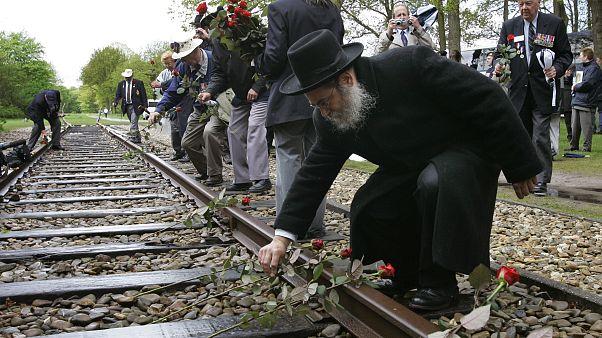 A rabbi places a rose on rail tracks near Westerbork, a former transit camp