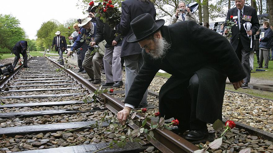 A rabbi places a rose on rail tracks near Westerbork, a former transit camp