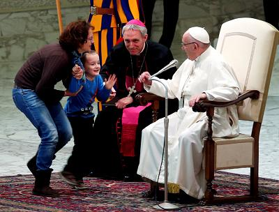 Pope Francis reacts as a child approaches him onstage during a general audience at the Vatican on Nov. 28, 2018.