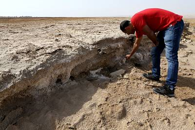 EcoPeace engineer Eshak Alguza breaks off a chunk of salt on what used to be the bottom of the Dead Sea.