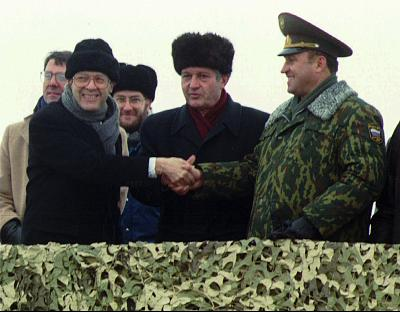 U.S. Defense Secretary William J. Perry, left, shakes hands with Ukraine Defense Minister Valery Shmarov, center, and Russian Defense Minister Pavel Grachev as they stand over the crater which formerly housed a missile silo at a military base near Pervomaysk, Ukraine, on Jan. 5, 1996.