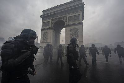 Tear gas surrounds riot police as they clash with protesters near the Arc de Triomphe on Saturday.