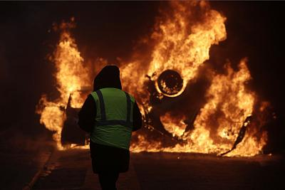 A protester watches a burning car near the Champs-Elysees in Paris on Saturday.