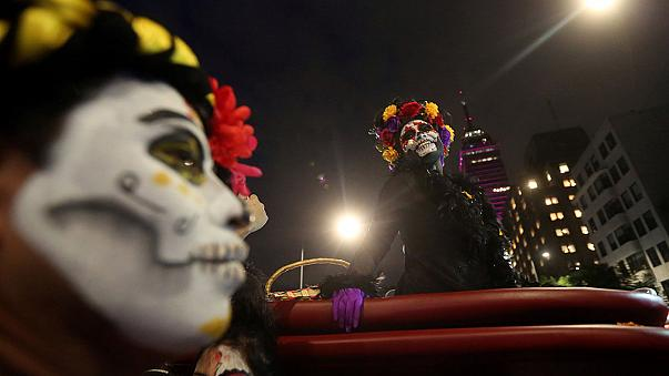 Mexicans don skeleton disguises for a pre-Day of the Dead parade