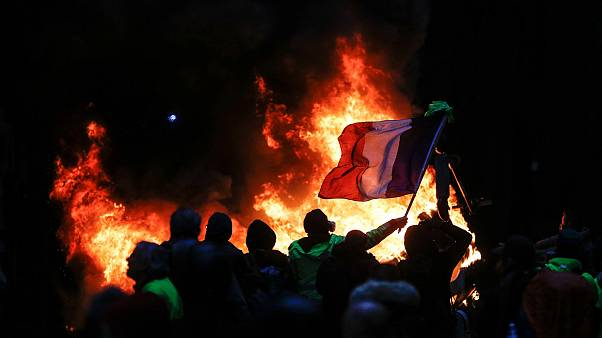 Image: Protestors fly a French flag during a protest of Yellow vests (Gilet