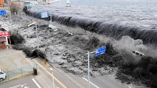 Waves approach Miyako City after a 9.0 magnitude earthquake hit Japan and t