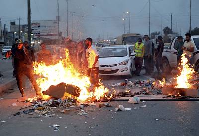 Protesters burn tires during a rally in Basra, Iraq, on Tuesday.