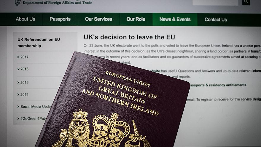 Image: A UK passport in front of a webpage for the Irish Embassy in Wells,
