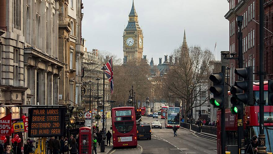 Image: Buses pass through traffic lights near the Houses of Parliament in L