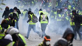 Image: Protesters run through tear gas in Paris on Saturday