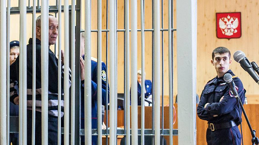 Mikhail Popkov stands inside a defendant's cage during a court hearing in I