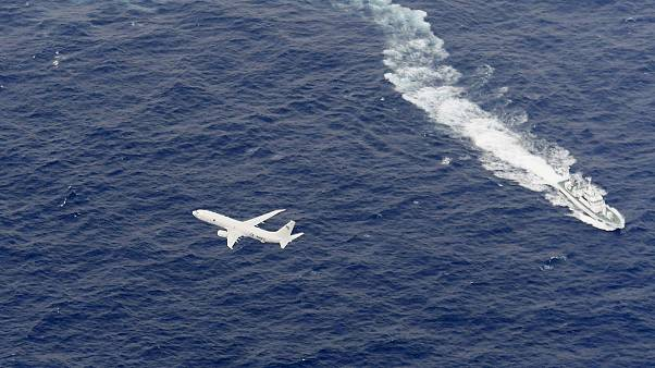 Image: A Japan Coast Guard patrol vessel and U.S. Navy airplane conduct sea