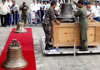 Philippine military personnel unload the three church bells on Tuesday.