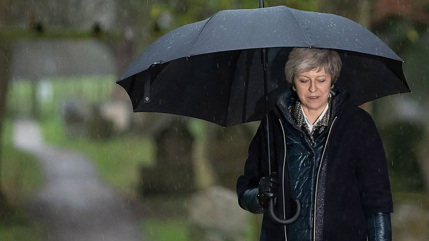 Image: Britain's Prime Minister Theresa May shelters from the rain under an