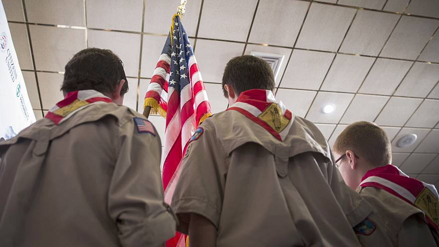 Image: Boy Scouts stand on stage with a U.S. flag during the Pledge of Alle