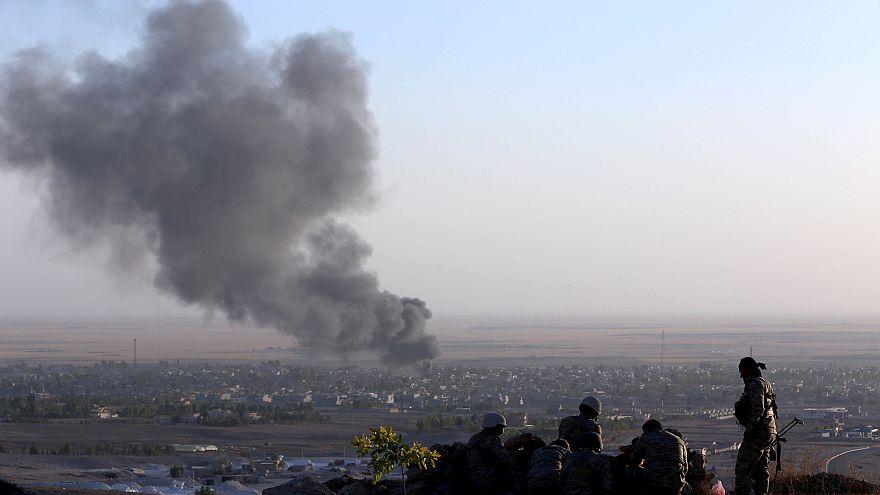 Image: Iraqi Kurdish Peshmerga fighters look on as smoke billows in the tow