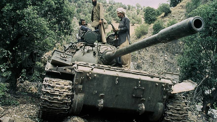 Image: Mujahedeen sit on a captured Soviet tank in Afghanistan in 1987.