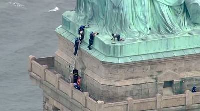 Police talk to Theresa Okoumou, who was charged with climbing the base of the Statue of Liberty in New York on July 4, 2018.