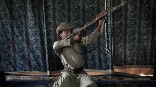 Image: Kahlan, a 12-year-old former child soldier, demonstrates how to use